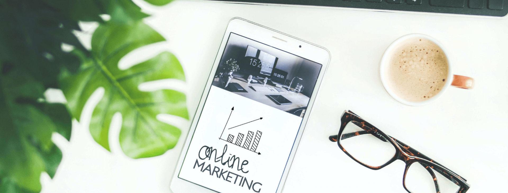 """Handy mit Text auf Display """"Online Marketing"""", Tastatur und Brille"""
